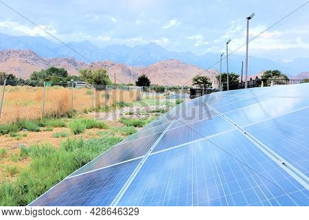 Solar Panels Transferring Sunlight Into Energy On An Arid Field Taken At A Rural Community In The Gr
