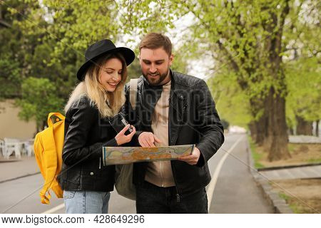 Couple Of Tourists With Map Planning Trip On City Street