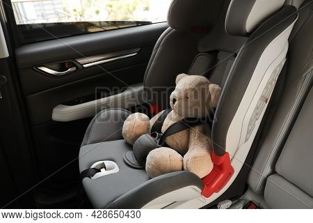 Teddy Bear Fastened With Car Safety Belt In Child Seat