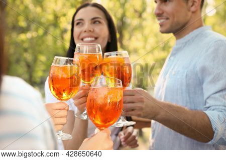 Friends Clinking Glasses Of Aperol Spritz Cocktails Outdoors, Focus On Hands