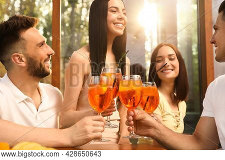 Friends Clinking Glasses Of Aperol Spritz Cocktails At Outdoor Cafe