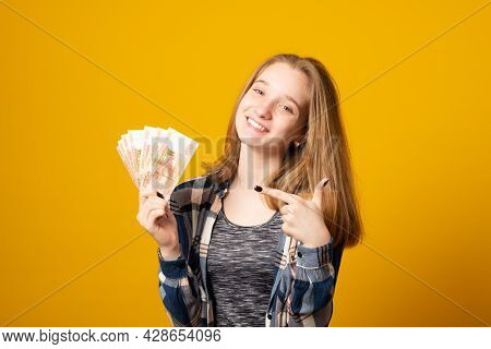 Portrait Of Happy Beautiful Young Woman Holding Rubles Money Isolated Over Yellow Background. Sale,