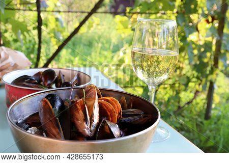 Boiled Mussels In Cream Sauce With Parsley In Iron Bowl And Glass Of White Wine On White Table In Th