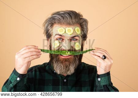 Fun Aloe Vera Moustache. Funny Man Model With Clay Mask And Cucumber Slices On Face. Spa, Dermatolog