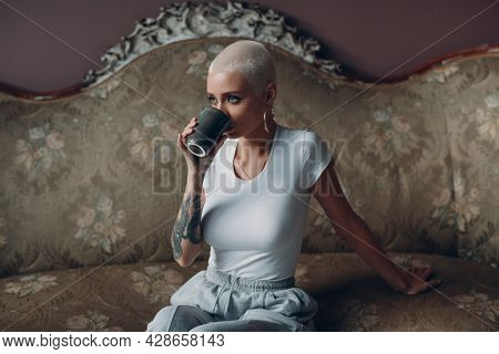 Millenial Young Woman With Short Blonde Hair Portrait Sitting With Cup Of Tea Or Coffee Drink On Vin