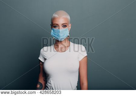 Millenial Young Woman In Medical Protective Face Mask With Short Blonde Hair Portrait Standing Indoo