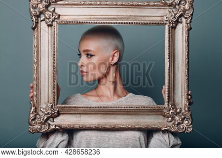 Millenial Young Woman With Short Blonde Hair Holds Gilded Picture Frame In Hands Behind Her Face Pro