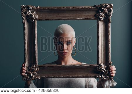 Millenial Young Woman With Short Blonde Hair Holds Gilded Picture Frame In Hands Behind Her Face Por
