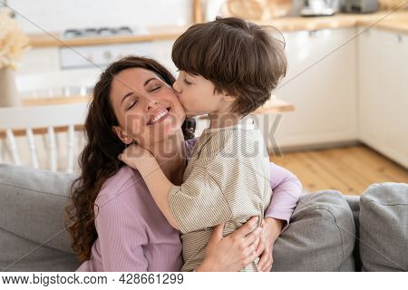 Young Caring Family Together: Cute Kid Boy Giving Mummy Loving Kiss Express Love And Care. Small Son