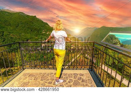 Elegant Woman At Sunset On Top Of Lugano Swiss City By Lugano Lake In Switzerland. Aerial View Looko