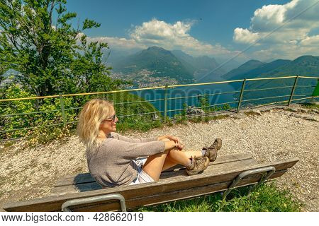 Swiss Girl Sitting On Top Of San Salvatore Mount By Lugano Lake In Switzerland. Aerial View Lookout