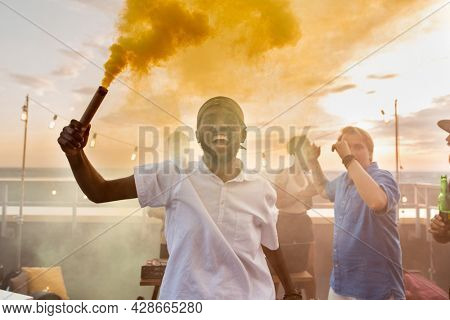 Young ecstatic African man with yellow smoke cracker against his friends