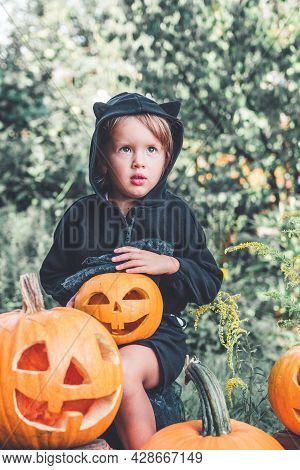 Child Dressed In Black With Jack-o-lantern In Hand, Trick Or Treat.