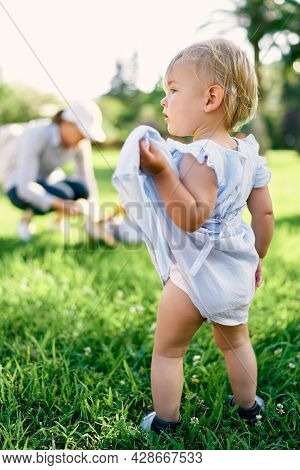 Little Girl Stands On A Green Lawn, Lifting The Hem Of Her Dress With Her Hand