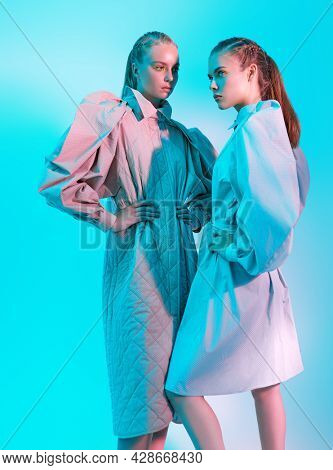 Haute couture clothing. Two fashion models pose in stylish clothes from the spring-summer collection. Full length studio portrait in aquamarine light.