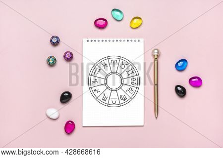 Horoscope Circle With Twelve Signs Of Zodiac On Paper, Divination Dice, Colorful Stone On Pink Backg