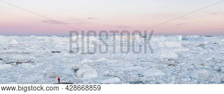 Travel in arctic landscape nature with icebergs. Greenland tourist man explorer tourist person looking at amazing view of Greenland icefjord affected by climate change and global warming.