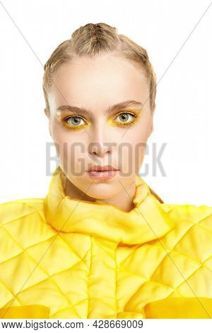 Close up portrait of a beautiful blonde girl model with colored yellow arrows on her eyes and in bright yellow clothes on a white background. Make-up and cosmetics. Beauty and fashion concept.