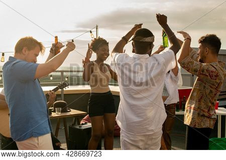 group of young ecstatic intercultural friends dancing at rooftop party