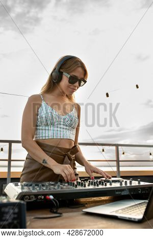 Happy young female deejay mixing sounds on soundboard at outdoor party