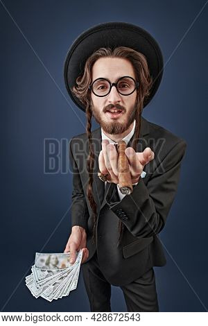 Rich Jew concept. Portrait of a wealthy Jewish man with a gold ring on his finger and a bundle of banknotes, who smokes a cigar. Studio shot on a dark blue background.