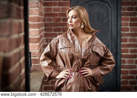 Stylish middle-aged woman with enlarged full lips poses in a leather coat in loft interior. Luxury lifestyle. Female beauty, fashion.