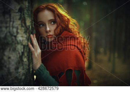 Portrait of beautiful red haired girl in a traditional green celtic dress and a red cloak is in forest. Historical reconstruction of ancient Celtic times.