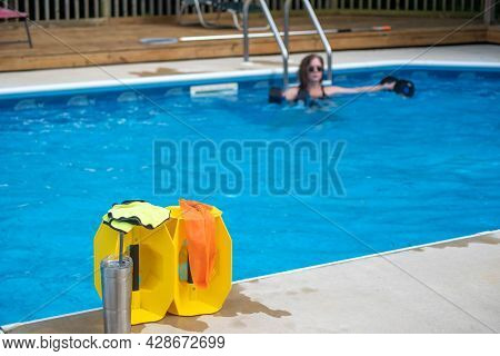 Closeup Of Pool Exercise Equipment In Foreground Of Sunny Residential Pool Scene With One Woman Doin