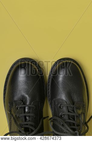Fashionable Youth Black Leather Autumn Boots On Yellow Background Flat Lay Top View. Stylish Womens