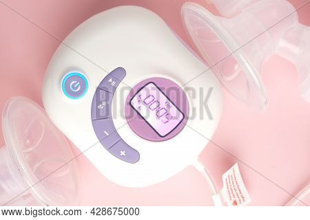 Close Up Picture Of Portable Lactation Breast Pump On Pink Background. Battery And Direct Power Supp