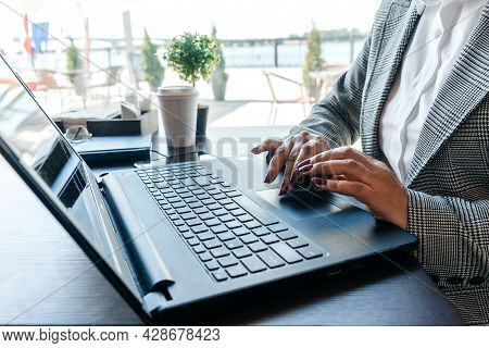 Hands Typing In Notebook. Window On Background.