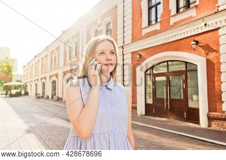 Young Woman Talking On Mobile Phone Outdoors.
