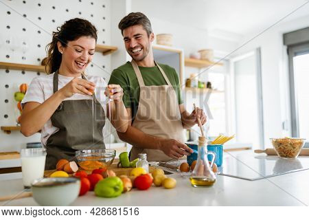 Young Happy Couple Is Enjoying And Preparing Healthy Meal In Their Kitchen
