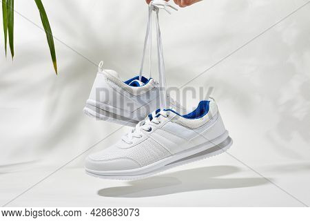 The Hand Holds By Shoelaces White Sneakers. Hand Hold Sporty Shoes On A White Background With Palm L