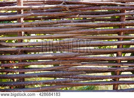 Wooden Fence. Background From Intertwined Branches Of A Vine