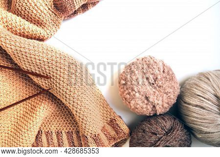 Balls Of Woolen Yarn Of Different Colors And A Knitted Beige Sweater, Knitting Needles On A White Ba