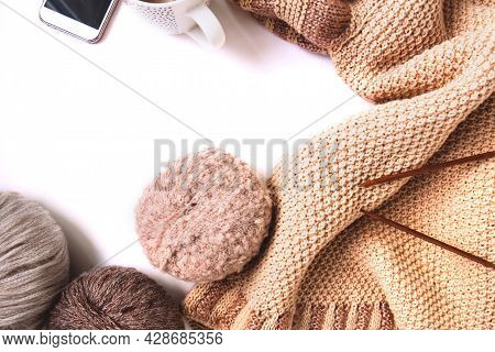 Balls Of Woolen Yarn Of Nude Colors And A Knitted Beige Sweater, Knitting Needles, Mobile Phone On A