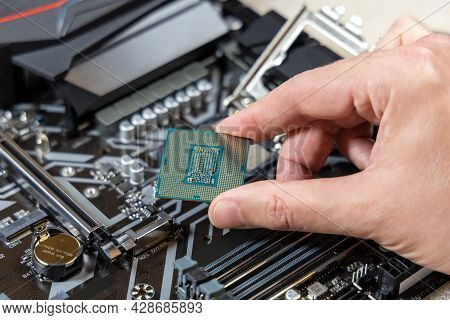 A Technician Holds The Cpu Against The Background Of The Motherboard. Computer Parts. Pc Assembly Co