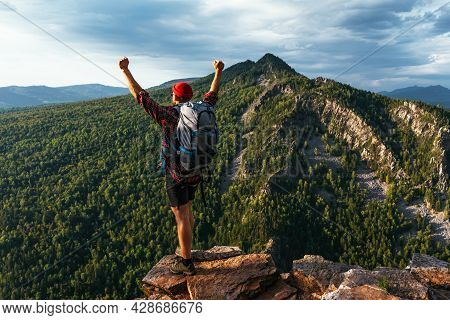 Hiker With Arms Up Standing On The Top Of The Mountain. A Man With A Backpack In The Mountains At Su