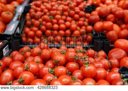 Variety Of Tomatoes On The Farmers Market, Tomatoes And Small Cherry Tomato In Boxes At Market Stall