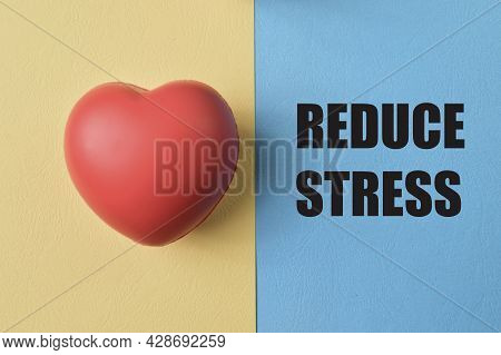 Red Heart Shape Isolated On Yellow And Blue Background With Text Reduce Stress