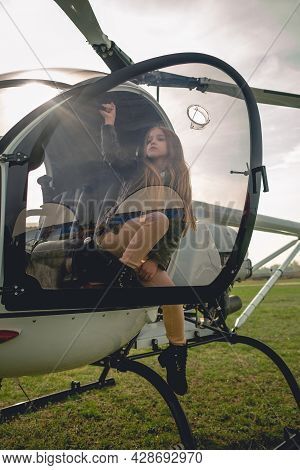 Preteen Girl Sitting In Open Cockpit Of Landed Helicopter