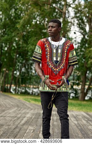 An African Man In South African National Clothes, A Black Young Man Resting In A Park In National Cl