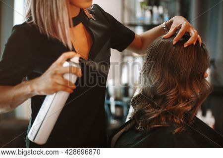 Hairstyling Process In Beauty Salon. Cropped Shot Of Female Hairdresser Fixing Customer Woman Hair W
