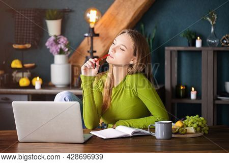 Young Pensive Woman Freelancer Sitting At Table At Home With Laptop, Making Notes, Staring Thoughtfu