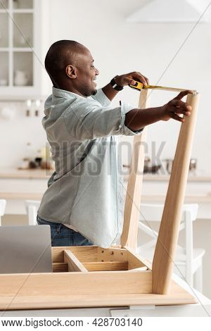 Black Millennial Handyman Assembling Wooden Table And Measuring The Width Between Legs, Standing In