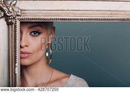 Millenial Young Woman With Short Blonde Hair On Gilded Picture Frame. Cropped Face Of Beautiful Myst