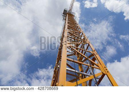 Construction Crane Against The Blue Sky. Beige Crane At The Construction Site.