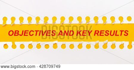Torn Paper Strip On Yellow Background With Text Objectives And Key Results