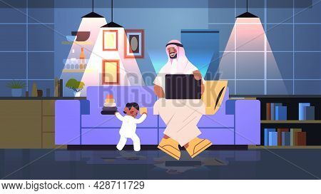 Busy Arab Father Working At Home Man Using Laptop Little Son Playing With Toys Freelance Fatherhood